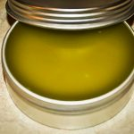 green herbal salve in a silver tin with the lid propped on the edge