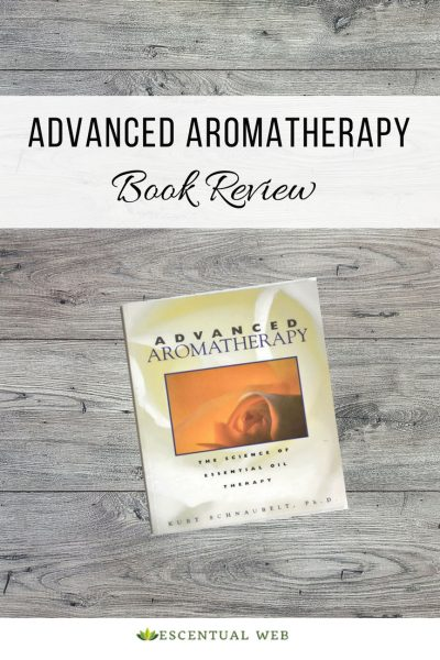 The book Advanced Aromatherapy by Kurt Schnaubelt on a wooden background, text says it is a book review