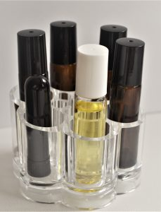 Acrylic lipstick holder with roller ball bottles and a nasal inhaler on a white background